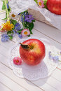 Red apple on white garden table