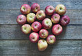 Red apples heart shape by over wooden table Royalty Free Stock Photos