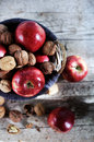 Red apples and walnuts in shells filled in basket autumn scene shiny wooden on the wooden desk outdoors fall Royalty Free Stock Image