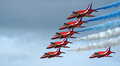Red arrows close flyby a by the trailing blue and white smoke behind at duxford air show sept picture is ideal for shows and Royalty Free Stock Photography