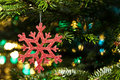 Red artificial snow flake in a christmas tree Royalty Free Stock Image