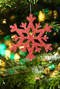 Red artificial snow flake in a christmas tree Stock Photography