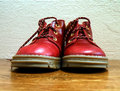 Red baby shoes or kid on wood floor Stock Photos