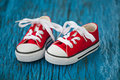 Red baby sneakers on blue background wooden Royalty Free Stock Photos