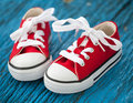 Red baby sneakers on blue background wooden Royalty Free Stock Images