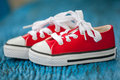 Red baby sneakers on wooden blue background Royalty Free Stock Image