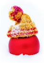 Red ball in knitted cap in the snow christmas with a pompon fresh Royalty Free Stock Image