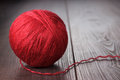 Red ball of threads on wooden table Stock Photos