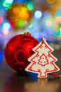 Red ball and white wooden christmas tree on a background of ligh lights Royalty Free Stock Images