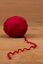 Red ball of yarn on a wooden background Stock Photos