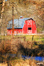 Red barn and creek a peek through the trees of a large nice with common white trim details bare branch trees a blue in the Stock Photo