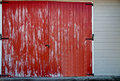 Red barn faded door with black latches on a white building Stock Photo
