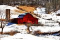 Red barn in the mountains of north carolina barns dot the landscape beautiful surrounded by a lite snowfall Royalty Free Stock Image