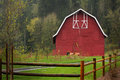 Red barn a nice with typical common details sitting in green field with rail fence in forefront and a hill of trees in Royalty Free Stock Photos