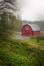 Red barn in rain a nice with typical common details sitting green field with bushes the forefront and a hill of trees Stock Images