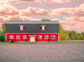 Red barn with tractor and sunset a yet to be tilled field before a beautiful against a orangie pink sky near Royalty Free Stock Photos