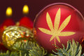Red bauble with the golden shape of a weed leaf. series Royalty Free Stock Photo