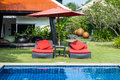 Red beach chairs with red umbrella aside swimming pool Stock Images