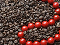 Red beads in brown beans Stock Photo