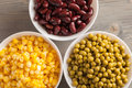 Red beans, green peas and sweet corn in white bowls Royalty Free Stock Photo