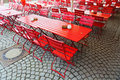 Red beer garden tables and chairs on cobblestones Royalty Free Stock Photos