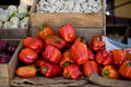 Red bell peppers onions garlic at local farmers market Royalty Free Stock Image
