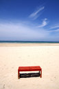 Red bench on the beach Royalty Free Stock Photo