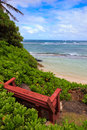 Red bench overlooking bathtub beach in oahu hawaii located on the northshore with a single the somewhat private Royalty Free Stock Photo