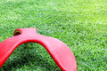 Red bench seat chair in three legs design on the green grass field Royalty Free Stock Photo