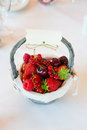 Red berry basket a full of berries stands on a restaurant table with white tablecloth Royalty Free Stock Photography