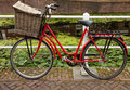 Red bicycle with basket parked beside canal in holland equipped a large a water riding bicycles is the most popular method of Stock Photography