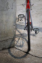 Red bicycle from behind in urban setting frame black tire rack silver crankset toe clips and black rim Stock Image
