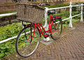 Red bicycle beside a canal in netherlands equipped with large basket parked water holland riding bicycles is the most popular Stock Photography