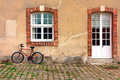 Red bicycle leaning against an old farmhouse wall stucco of a vintage farm building with aged cobblestone courtyard Royalty Free Stock Photography