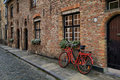 Red bicycle near the window in Bruges Royalty Free Stock Photo