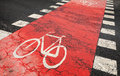 Red bicycle road marking on urban road asphalt crossing Royalty Free Stock Photos
