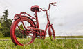 Red bicycle on the roadside small rusty painted in a in a rural area Royalty Free Stock Images