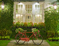 Red bicycle with white window and garden background Royalty Free Stock Photo
