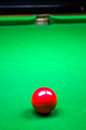 Red billiard ball in front of pocket on green baize table Stock Image