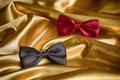 Red and black bow ties on golden tissue Royalty Free Stock Photos
