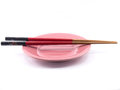 Red and black chopsticks and pink plate isolated on white background Royalty Free Stock Photo