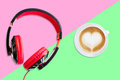 Red and Black earphones with white cup of hot coffee from top view on pink and green background. Pastel style Royalty Free Stock Photo