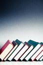 Red black and green books in a library row on white reflective surface Royalty Free Stock Image