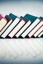 Red black and green books in a row on white reflective surface Royalty Free Stock Photography