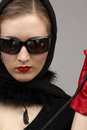 Red on black portrait of lady in headscarf and gloves with crop Stock Photo