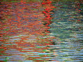 Red Blue Color pattern shimmers and reflects in ripples of water Royalty Free Stock Photo