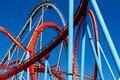 Red and blue colorful roller coaster rails, entertainment construction, sunny summer day at the amusement park Royalty Free Stock Photo