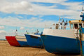 Red and blue fishing boats on the seashore Royalty Free Stock Photo