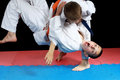 On the red and blue mat athletes are doing throws boys Stock Image
