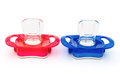 Red blue pacifiers white clipping path Stock Images
